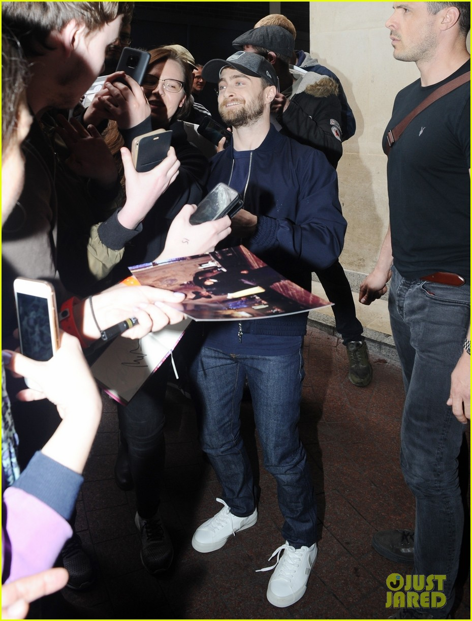 """Daniel Radcliffe poses for photos as fans hold out """"Harry Potter"""" photos for autographs this week in London."""