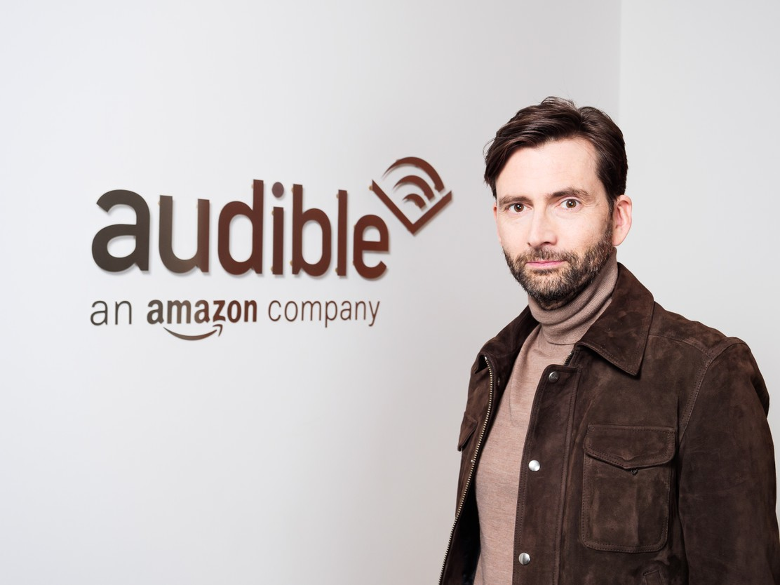 David Tennant poses in front of the Audible logo before heading into the studio.