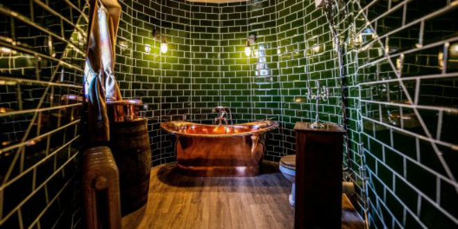 The bathroom's elegant, dark green tiles remind us of the Ministry of Magic.