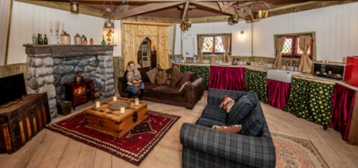 The interior of North Shire's Hagrid's Hut, a room with a cabin feel, soft sofa and armchair by the fire in a circular stone and wood room. It doesn't look as shabby as Hagrid's actual hut but it seems super cosy.