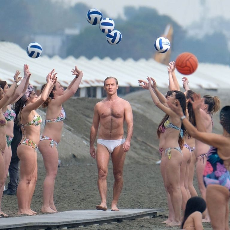 """Jude Law saunters along a boardwalk, framed by bikini-clad volleyball tossers while filming """"The New Pope""""."""