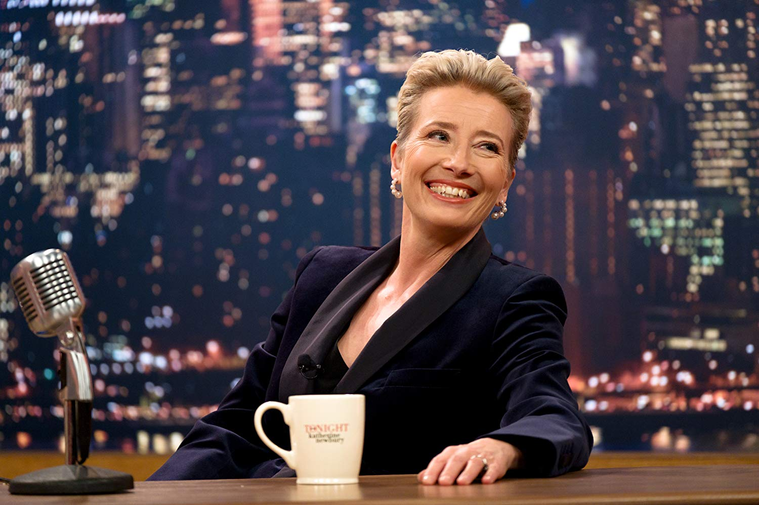 "Dame Emma Thompson smiles from behind her desk in this still from ""Late Night""."