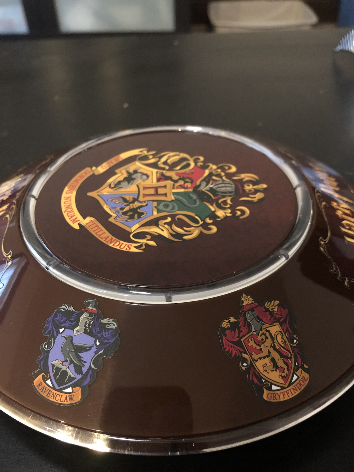 One side of the base has the Ravenclaw and Gryffindor House crests.