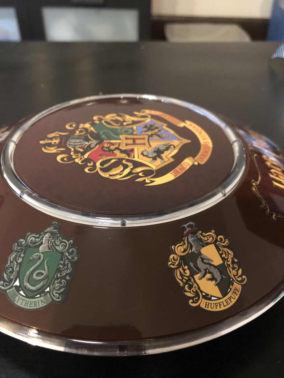 One side of the base has the Slytherin and Hufflepuff House crests.