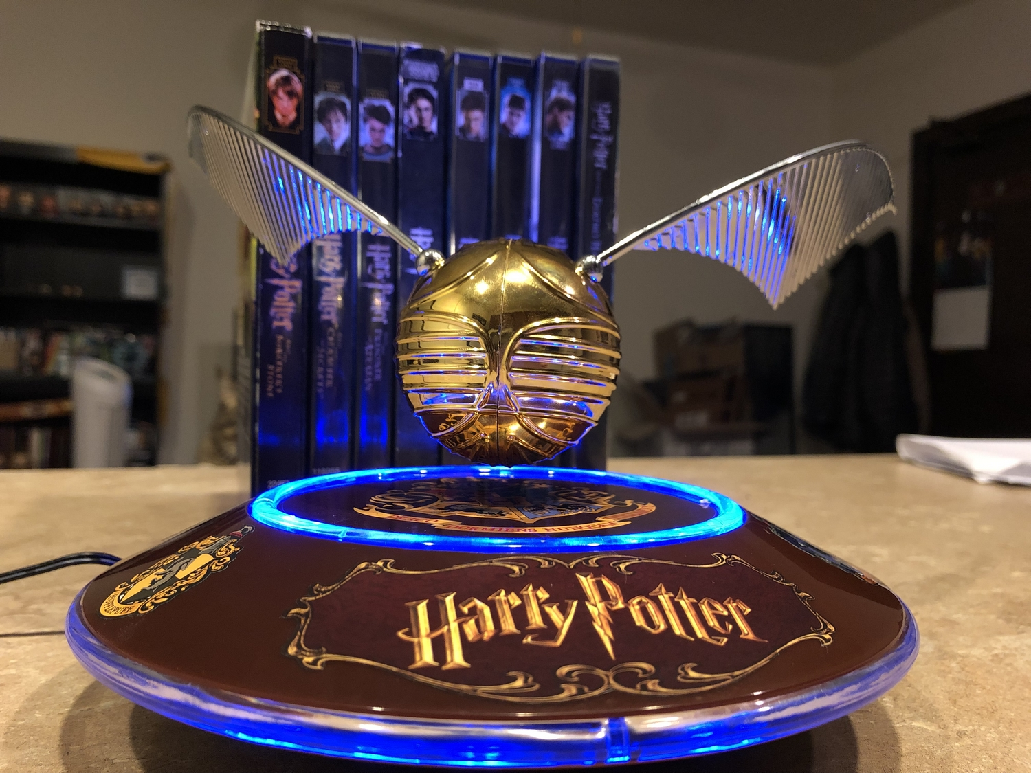 """Harry Potter GOLDEN SNITCH™, rotating on base in the light, with """"Potter"""" movie cases in the background"""