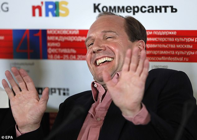 Ralph Fiennes laughs during a press conference in Moscow.