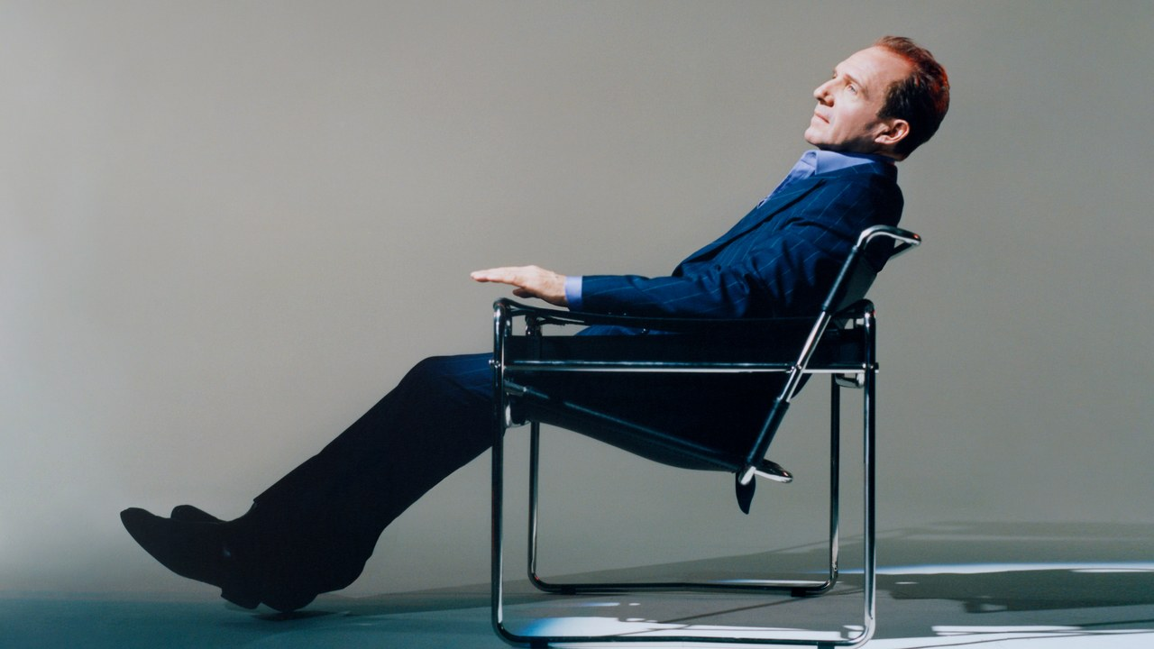 """Ralph Fiennes kicks back during a photo shoot for """"GQ""""."""
