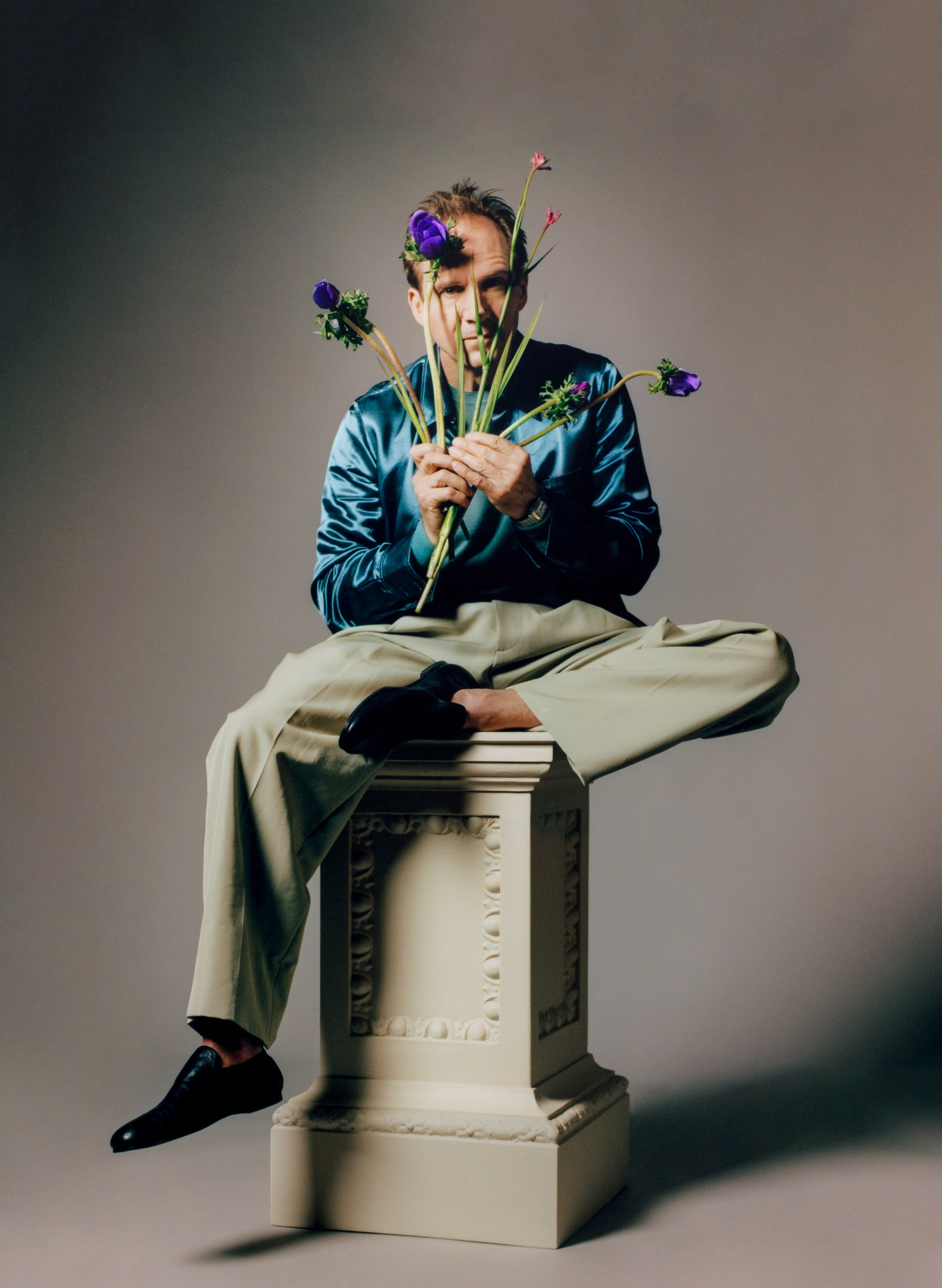 """Ralph Fiennes poses playfully during a photo shoot for """"GQ""""."""