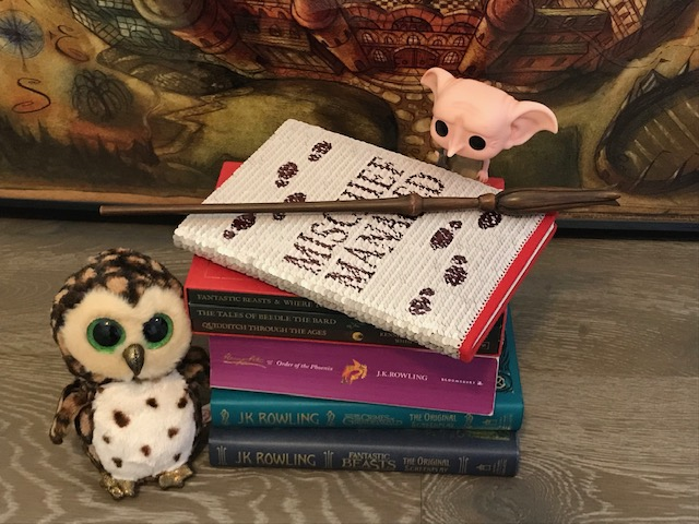 "Harry Potter: Manage Your Mischief Marauder's Map Sequin Notebook alternate cover, displayed on top of a stack of ""Harry Potter"" books with wand, Dobby figurine, and owl"