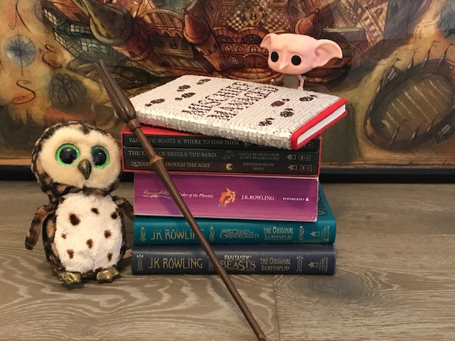 "Harry Potter: Manage Your Mischief Marauder's Map Sequin Notebook alternate cover, displayed with ""Harry Potter"" books, wand, Dobby figurine, and owl"