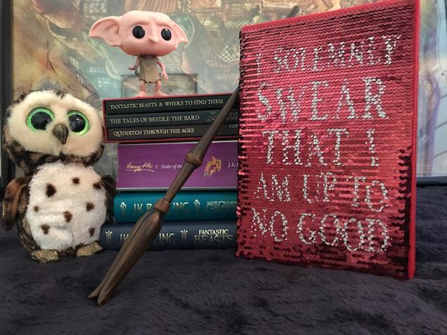 "Harry Potter: Manage Your Mischief Marauder's Map Sequin Notebook displayed with ""Harry Potter"" books, wand, owl, and Dobby figurine"