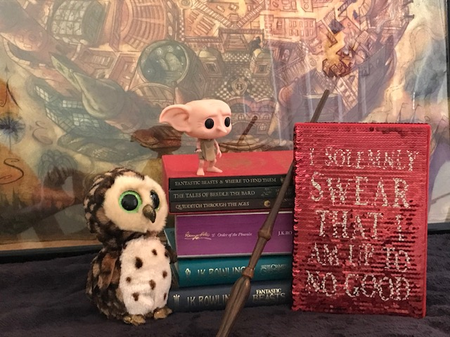"Harry Potter: Manage Your Mischief Marauder's Map Sequin Notebook displayed with ""Harry Potter"" books, wand, Dobby figurine, and owl"