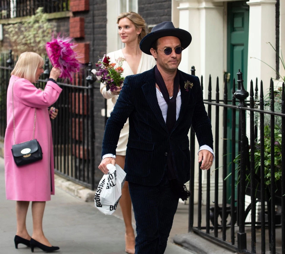Jude Law walks ahead of his new bride, Phillipa Coan, in Central London.