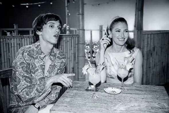 """Jamie Campbell Bower as Mick Jagger and Kelly Macdonald as Princess Margaret enjoy cocktails in a scene from """"Urban Myths""""."""
