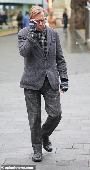 Timothy Spall adjusts his glasses as he makes his way into Global radio studios in London.