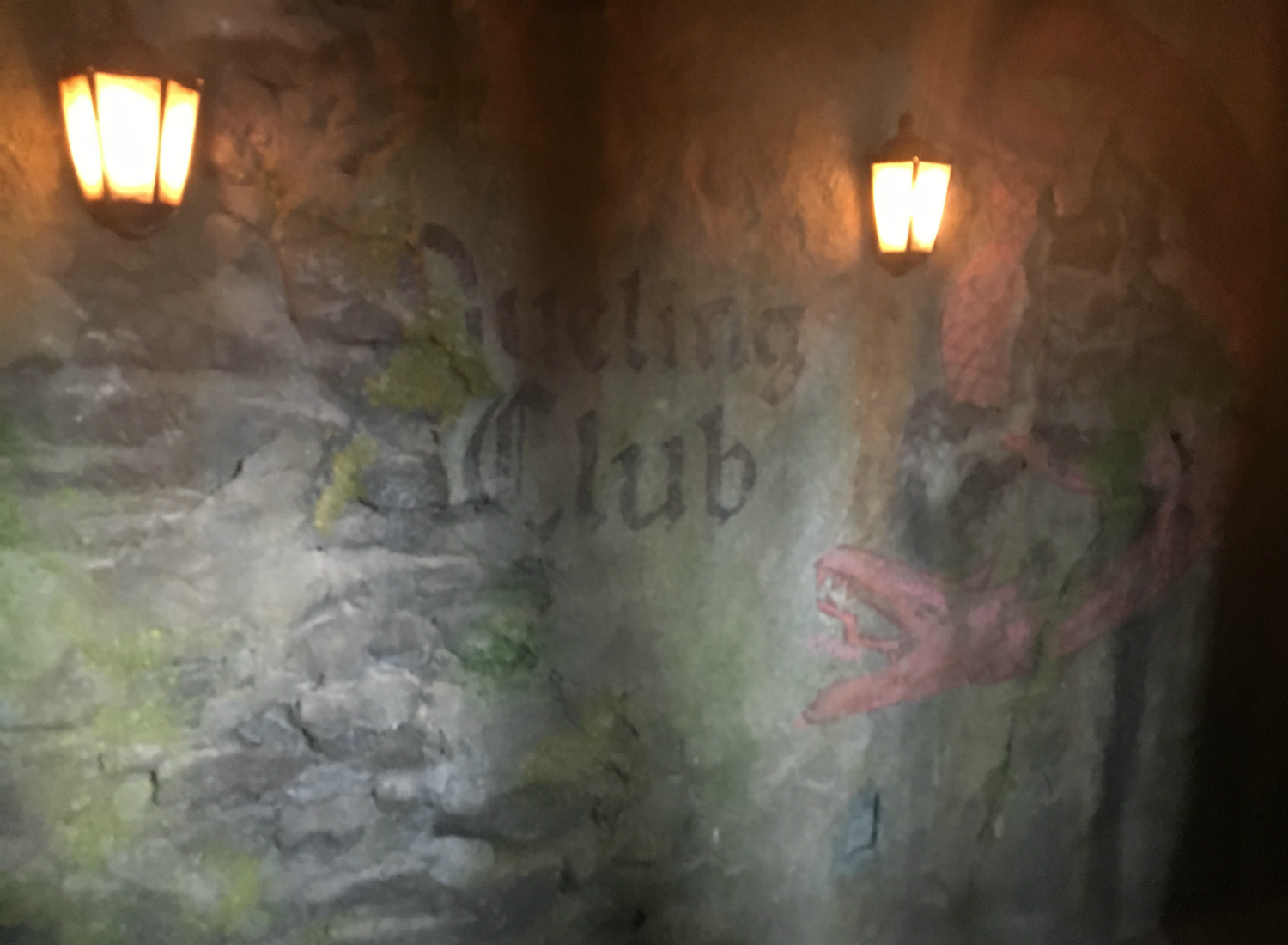 """On either side of this """"Dueling Club"""" notice is a dragon. The original ride in this location, which was rethemed to Dragon Challenge with the opening of Hogsmeade in 2010, was named Dueling Dragons."""