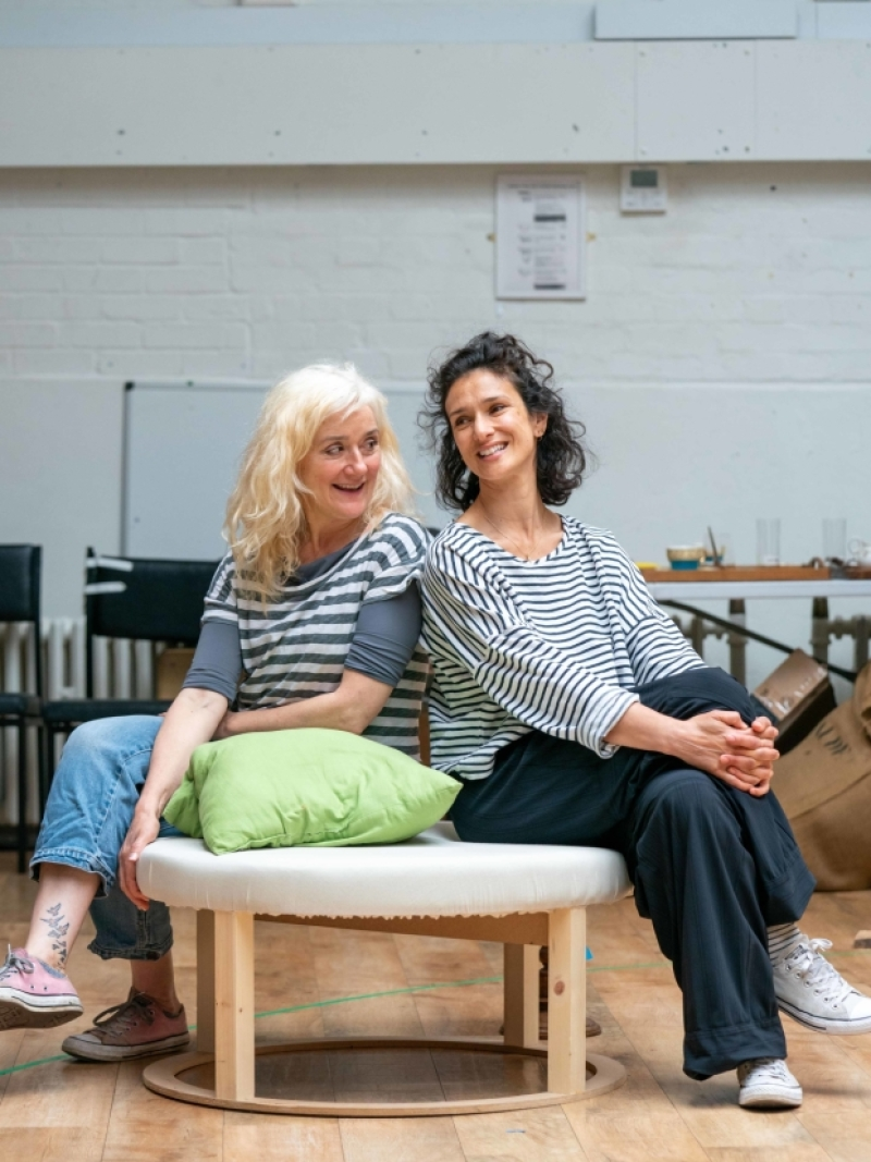 "Sophie Thompson smiles alongside Indira Varma during rehearsals for ""Present Laughter""."