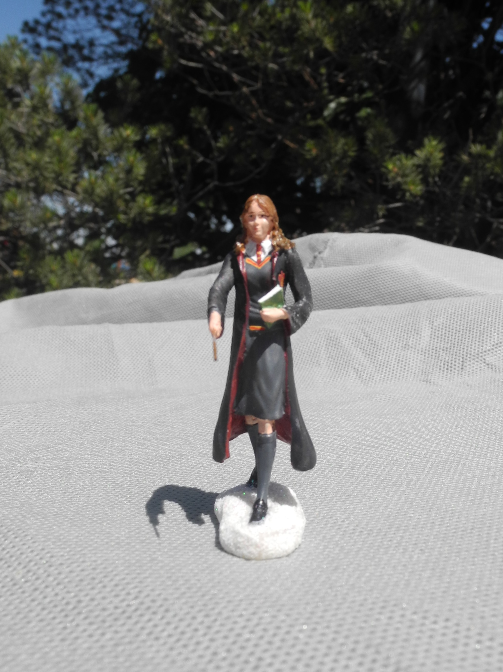 "The Bradford Exchange's ""HOGWARTS TRAIN STATION™"" free ""HERMIONE GRANGER™"" figurine is prepared for any situation with her customary book in one hand and her wand in the other."