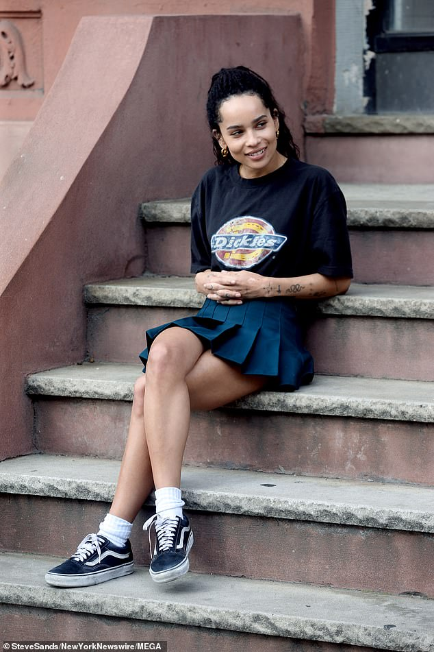 """Zoë Kravitz smiles from her seat on a set of steps during filming for """"High Fidelity""""."""