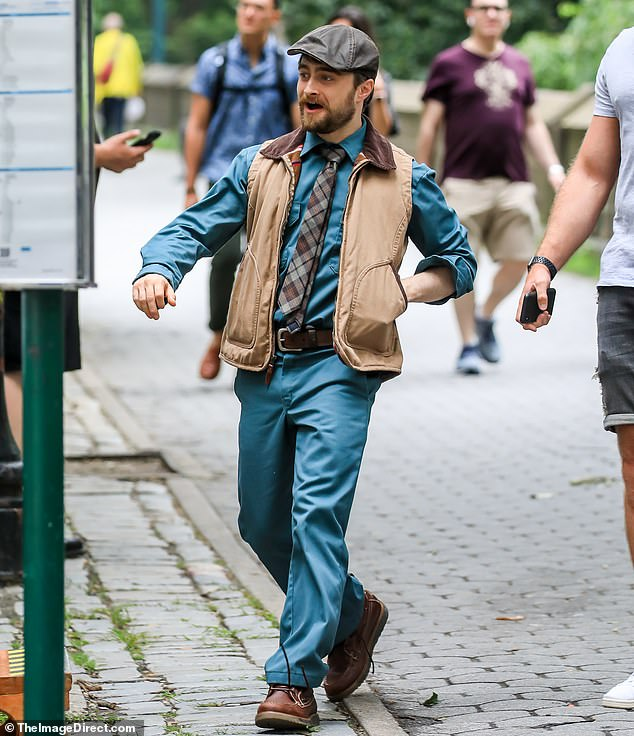 One of Radcliffe's costume changes includes a matching set – blue shirt and blue pants – with a plaid tie, tan vest, and newsboy cap.