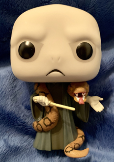 A close-up view of the Voldemort Funko Pop! figure, complete with his wand and Nagini wrapped around his neck