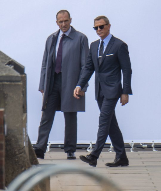 "Ralph Fiennes as M walks with Daniel Craig as James Bond during filming for ""Bond 25""."
