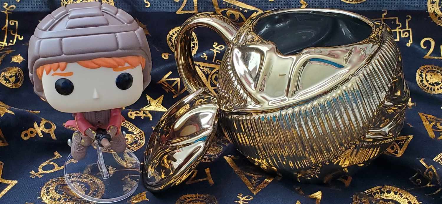 Ron Weasley Funko POP!, pictured with the Harry Potter Golden Snitch Coffee Mug from Hallmark Gold Crown, lid off
