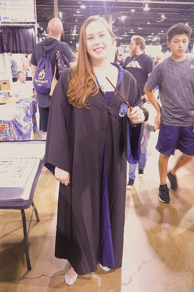 This Ravenclaw cosplayer is dressed in a Hogwarts robe and is holding a wand.