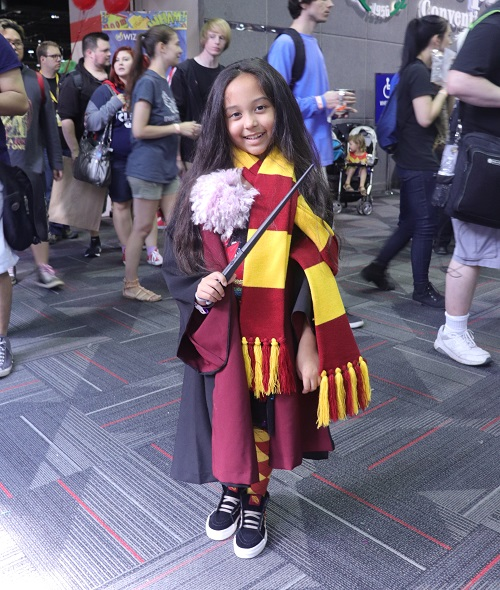 A child stands in front of a crowd wearing and red and yellow Gryffindor scarf and Hogwarts robes.
