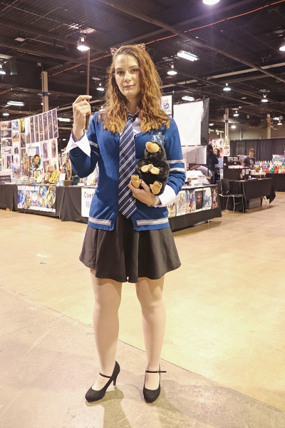 Holding a stuffed Niffler toy and a wand, this cosplayer wears a blue Ravenclaw sweater and poses in front of a vendor.