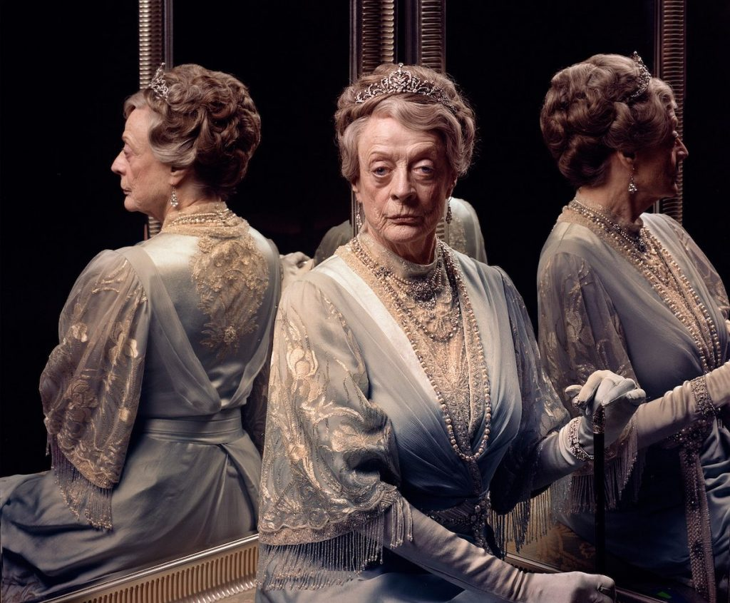 "Dame Maggie Smith in character as the Dowager Countess from ""Downton Abbey"" sits in front of a mirror."