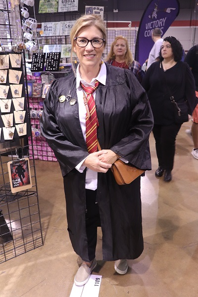 This cosplayer dressed in Gryffindor robes poses in front of a vendor.