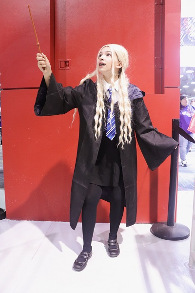 This cosplayer is wearing a blonde wig and dressed in Hogwarts robes and a blue tie.