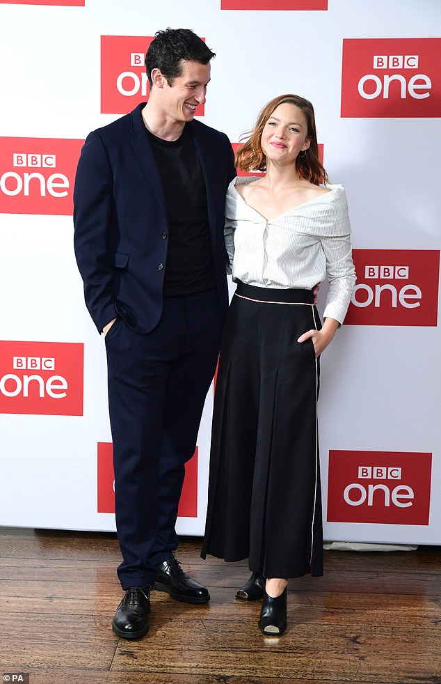 """Callum Turner and Holliday Grainger smile during a photo call for """"The Capture""""."""