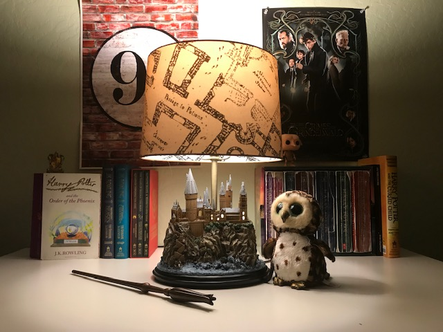 Harry Potter Hogwarts Lamp from The Bradford Exchange: pictured with other Harry Potter collectibles and books, with Hogwarts castle base and Marauder's Map lampshade illuminated