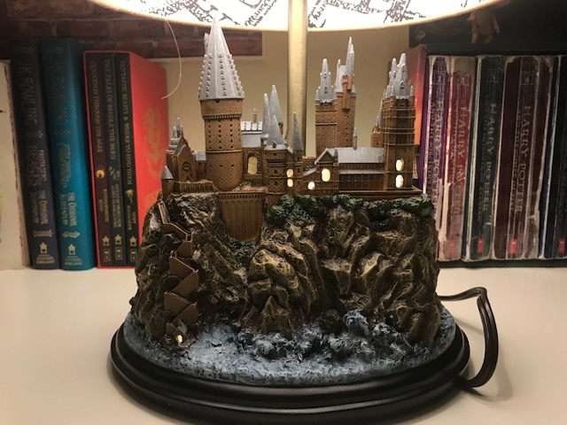 Harry Potter Hogwarts Lamp from The Bradford Exchange: pictured with other Harry Potter collectibles and books, close-up on Hogwarts sculpture base with windows illuminated