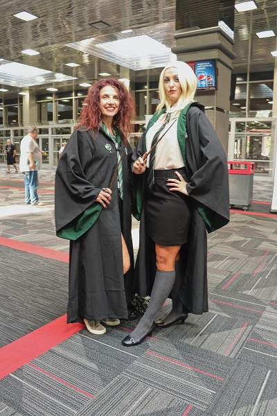 These cosplayers pose in the brightly lit lobby in Slytherin robes.