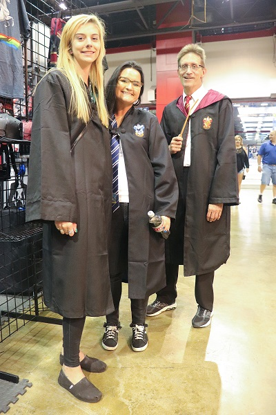 Three cosplayers dressed in Hogwarts robes.