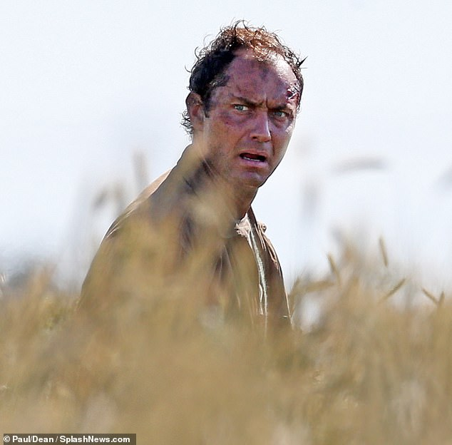 "Jude Law appears bloodied, beleaguered, and bedraggled during filming for ""The Third Day""."