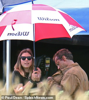 "Jude Law ducks under an umbrella when filming for ""The Third Day"" is briefly interrupted by rain."