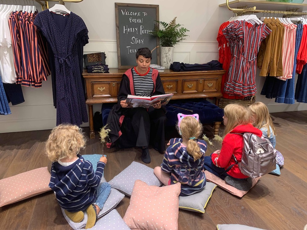 """A women dressed in Harry Potter robes reads a chapter of """"Harry Potter and the Philosopher's Stone"""" to a group of children who are sitting on the floor."""