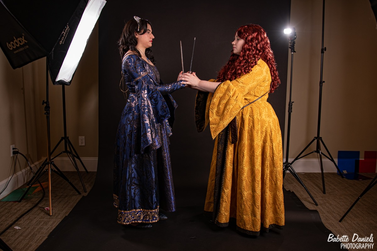 Rowena Ravenclaw and Helga Hufflepuff hold hands.