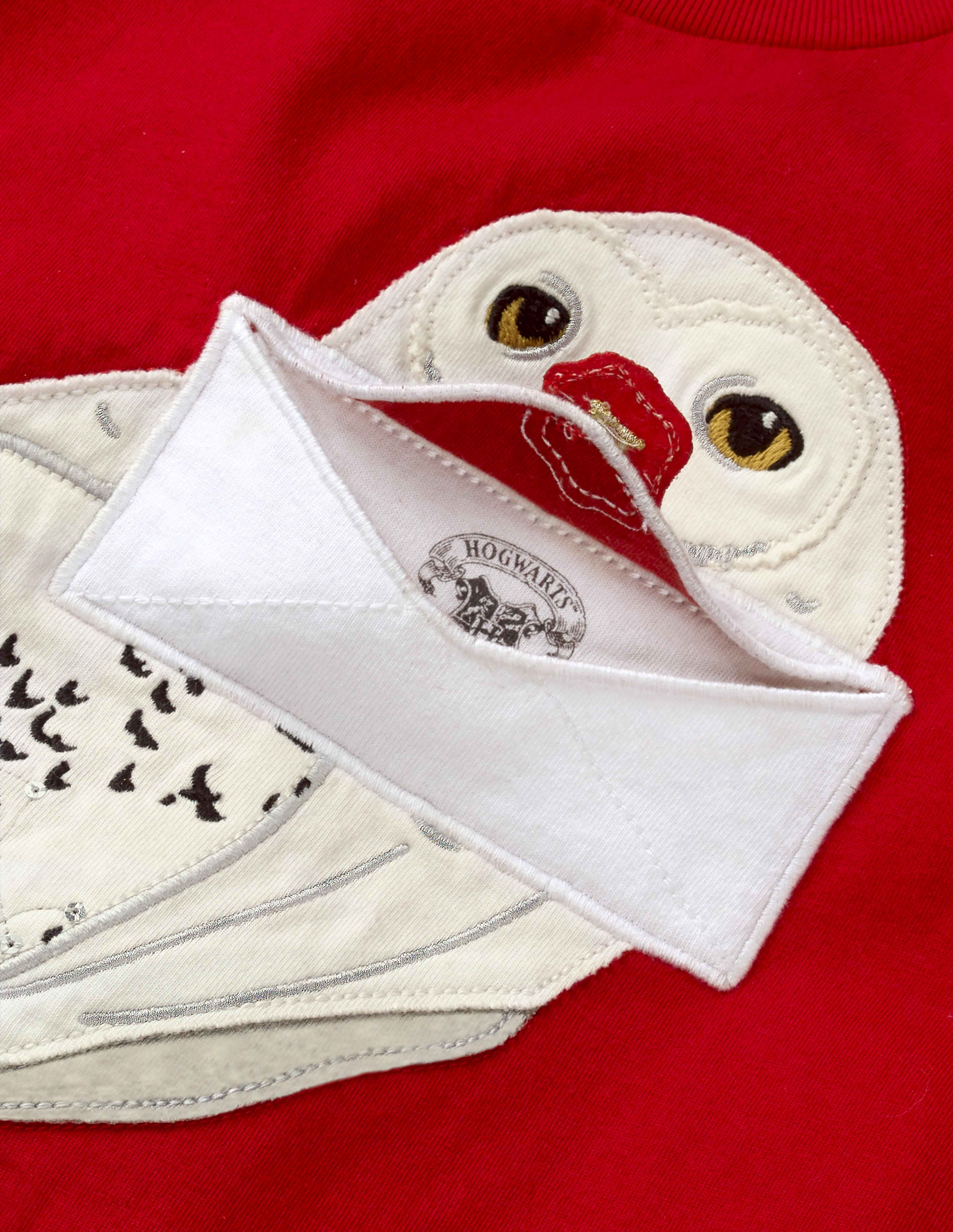 This close-up of the Mini Boden Hedwig Appliqué T-shirt in red shows how the flap of the envelope containing the Hogwarts acceptance letter lifts up to reveal the top of the Hogwarts seal. The shirt retails at £22.