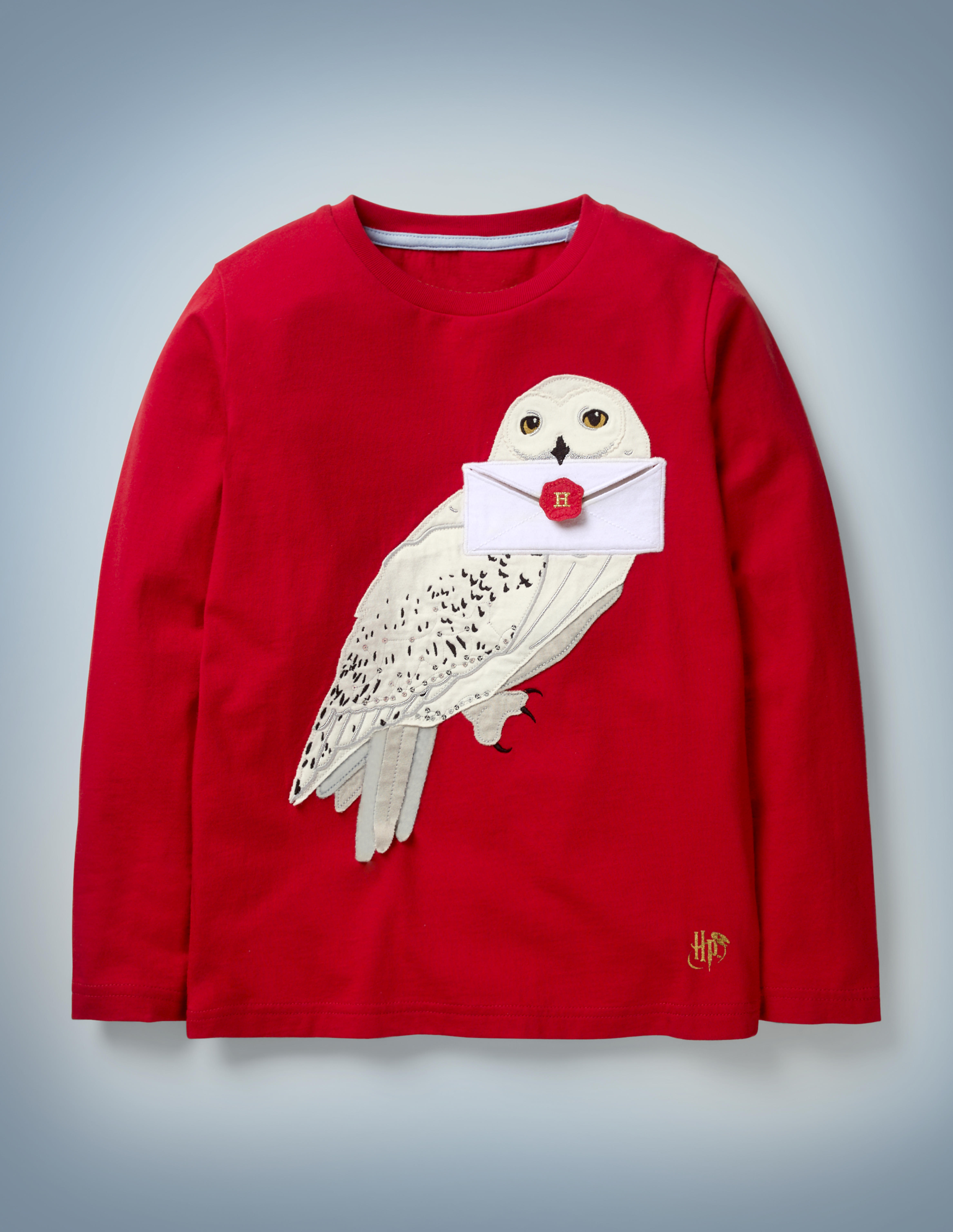 The Mini Boden Hedwig Appliqué T-shirt in red features an appliqué design of Harry Potter's beloved owl holding a Hogwarts acceptance letter in her beak. The shirt retails at £22.