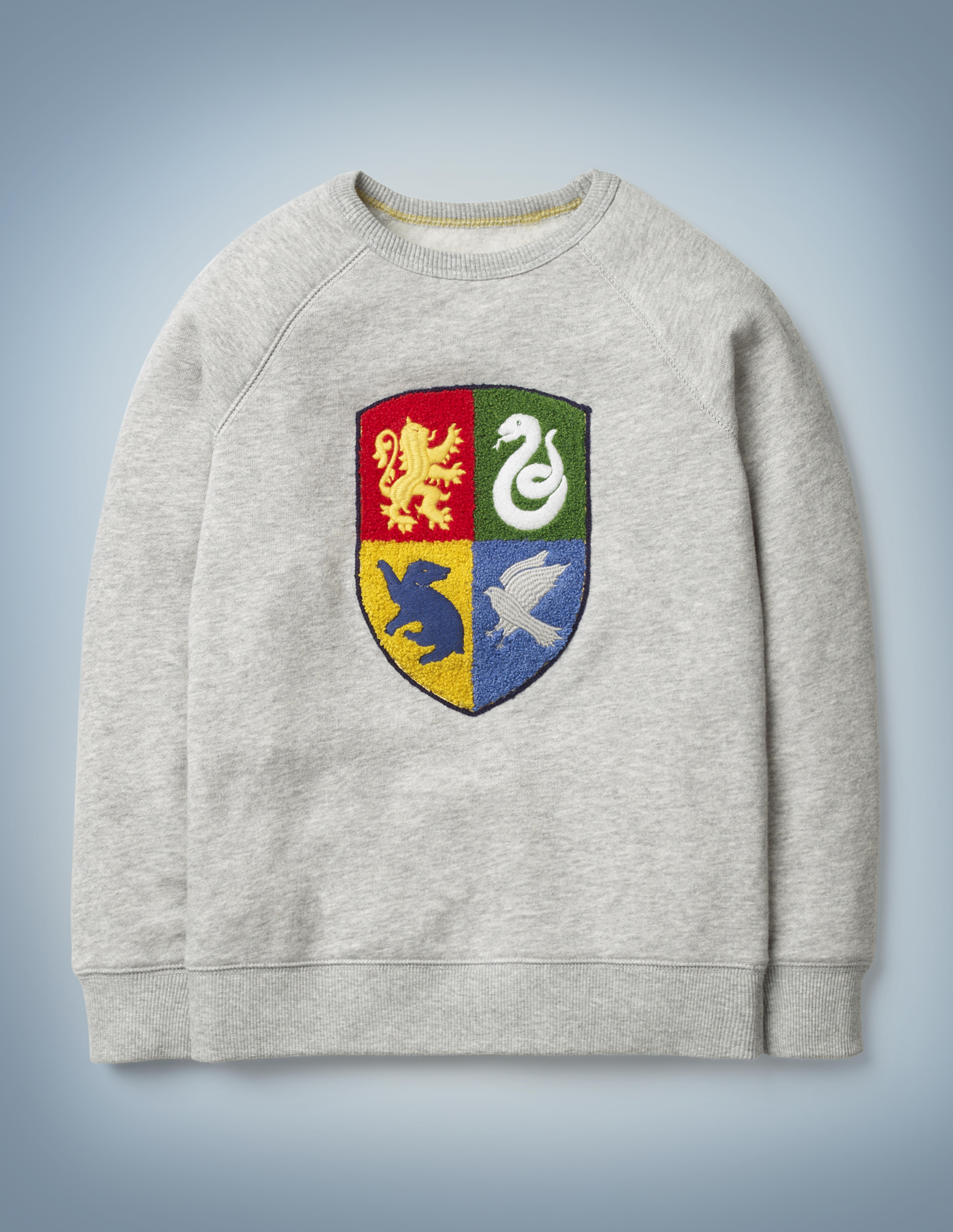 The Mini Boden Hogwarts Crest Sweatshirt in gray features a textured design showcasing the four Hogwarts House emblems. It retails at £28.