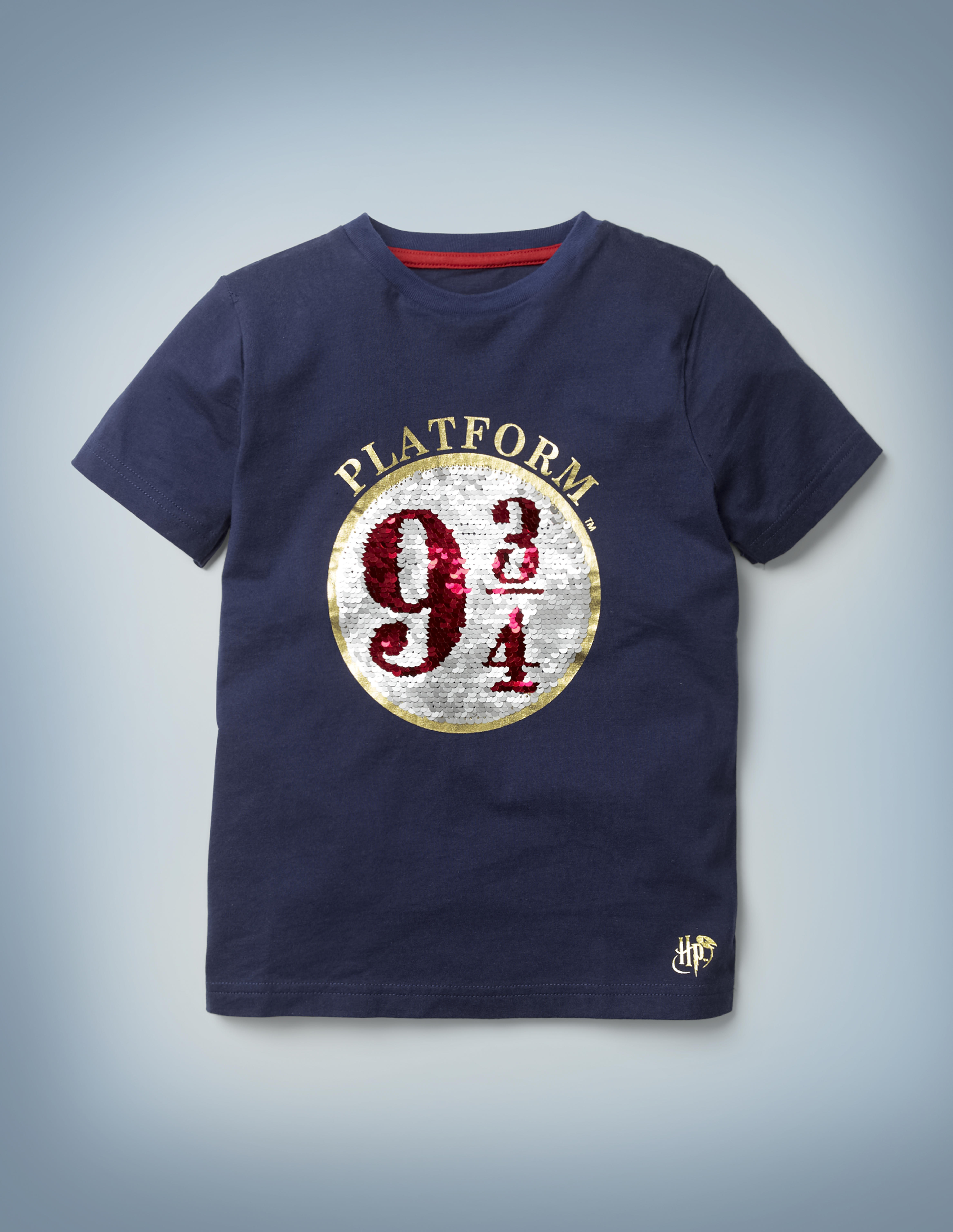 The Mini Boden Platform 9 ¾  Sequin T-shirt in blue features an eye-catching graphic of the circular 9 ¾ sign in silver and red sequins. It retails between £20 and £22.