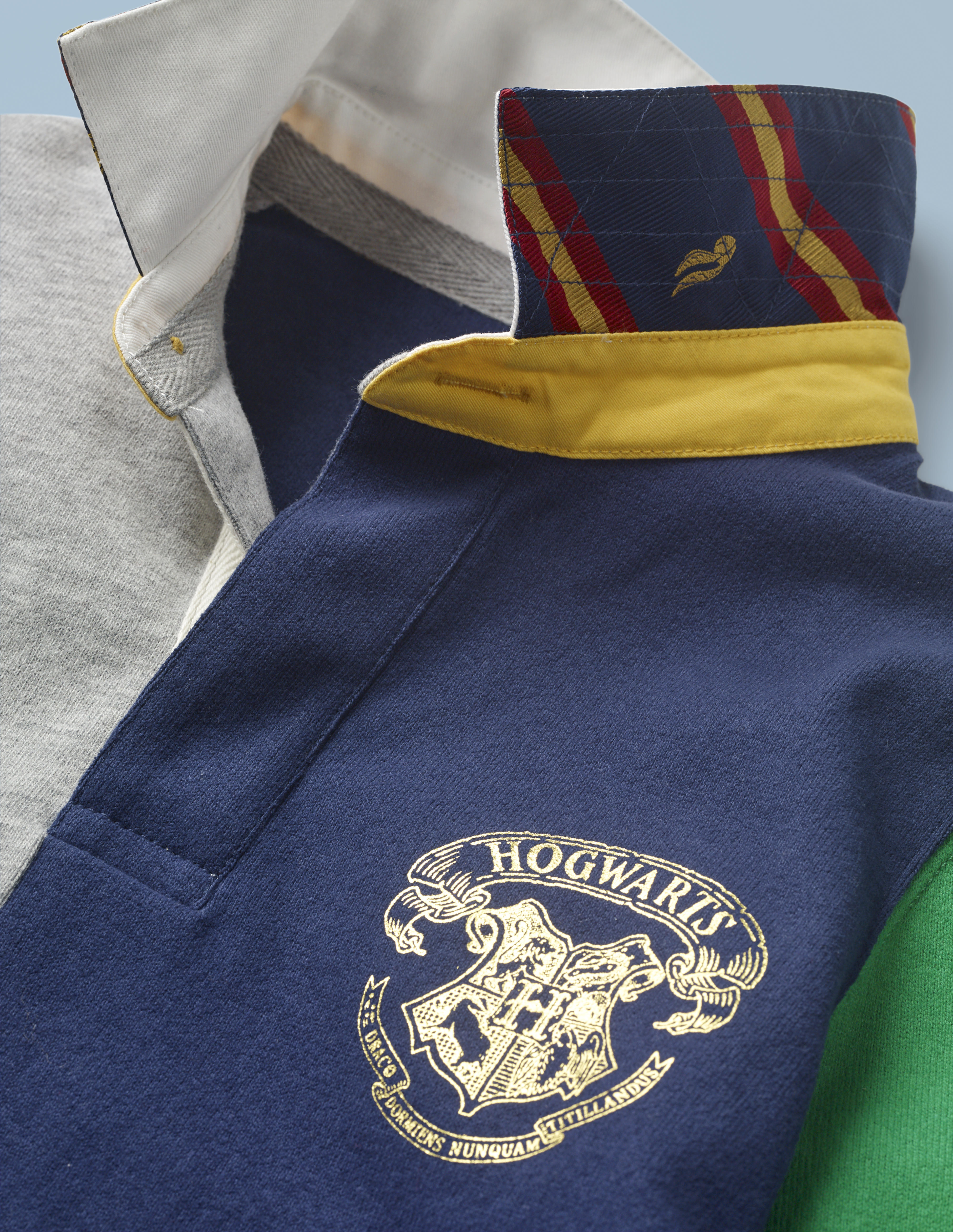 This close-up of the Mini Boden Hogwarts Rugby Shirt, multi-color, provides a better look at the collar design and Hogwarts crest in the front pocket area. It retails at £30.
