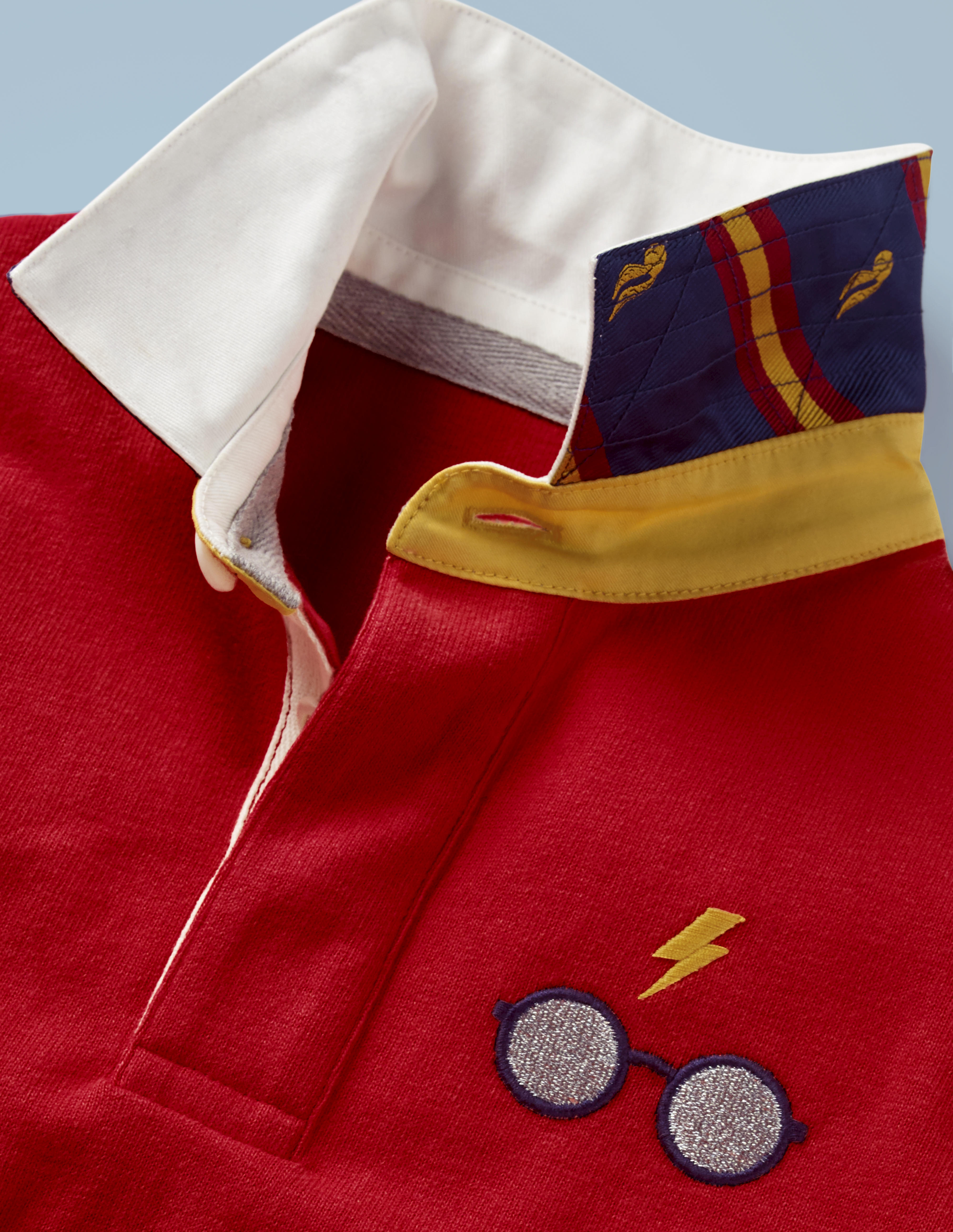 This close-up of the Mini Boden Hogwarts Rugby Shirt in red provides a better look at the collar design and glasses-and-scar logo in the front pocket area. It retails at £30.