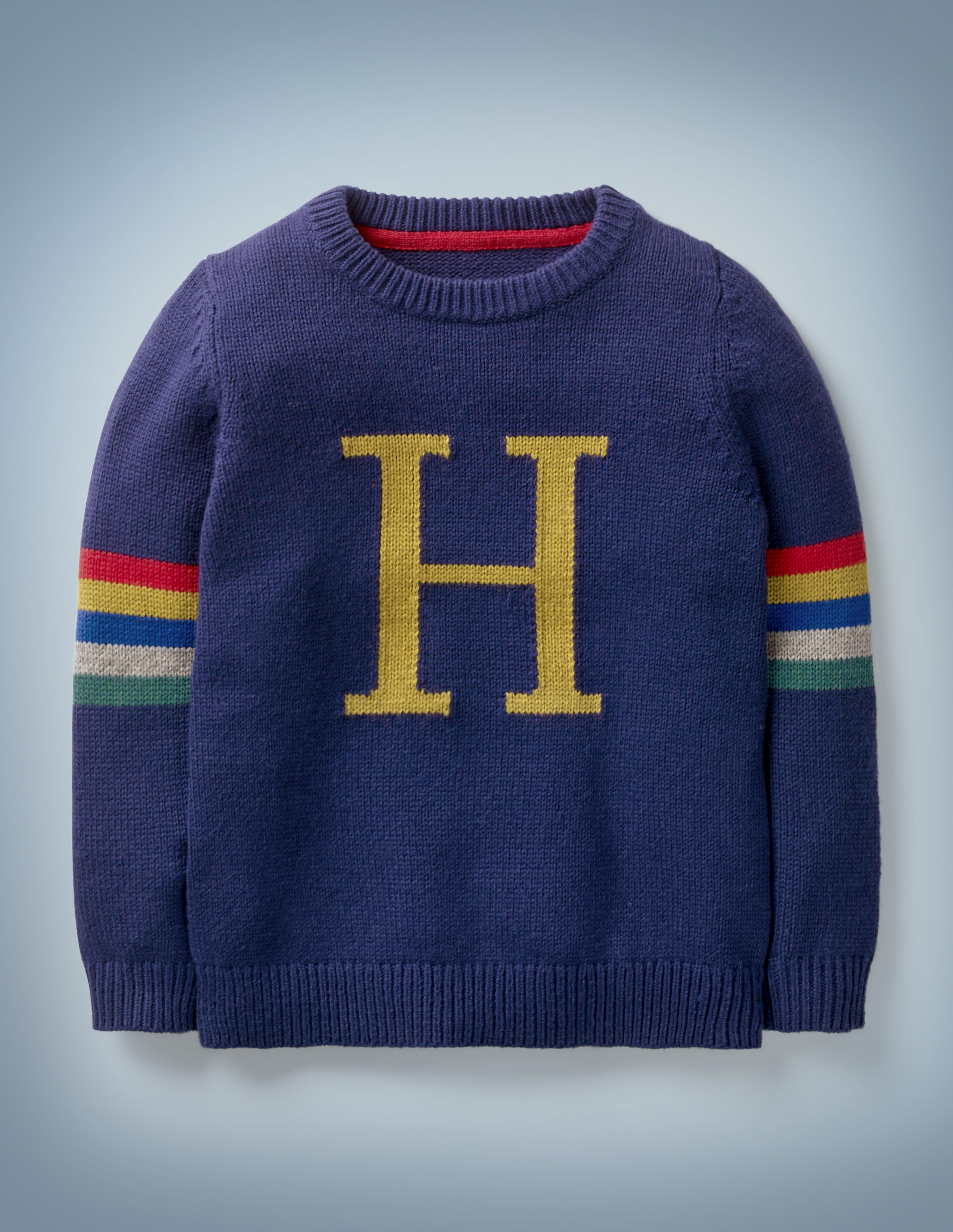 """The Mini Boden Harry Potter Knitted Jumper in blue is reminiscent of the Christmas sweater lovingly knitted for Harry by Molly Weasley. It features a large gold """"H"""" in the center with stripes in Hogwarts House colors on both sleeves. It retails between £32 and £37."""
