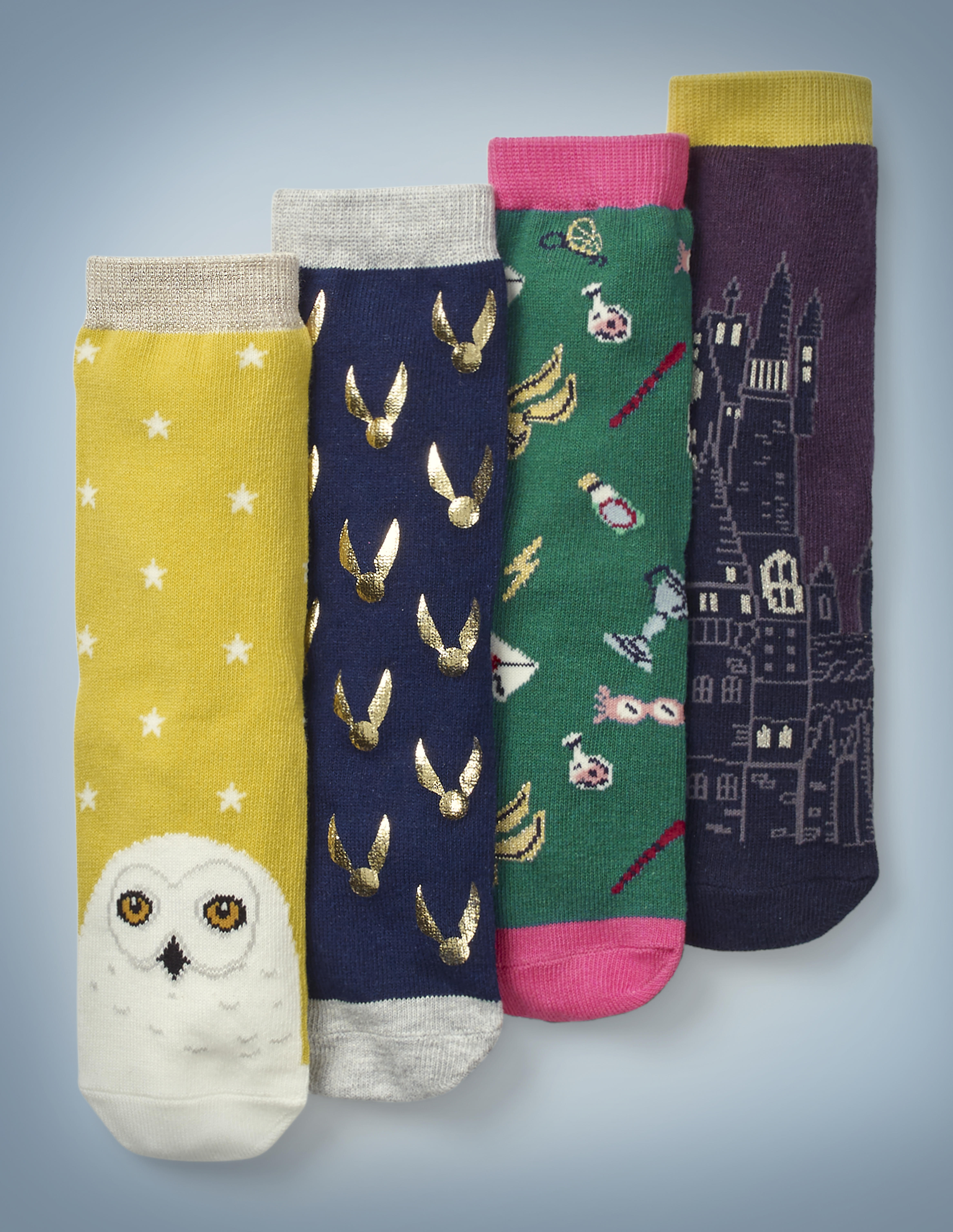 """The Mini Boden Pack of Harry Potter Socks features four different designs. Hedwig's face adorns the toe of a gold pair of socks with a white star pattern. Shiny Golden Snitches cover a navy blue pair. Iconic """"Harry Potter"""" items, such as Luna Lovegood's Spectrespecs and Hogwarts acceptance letters, cover a green and pink pair. An image of Hogwarts adorns a plum and gold pair. The pack retails at £18."""